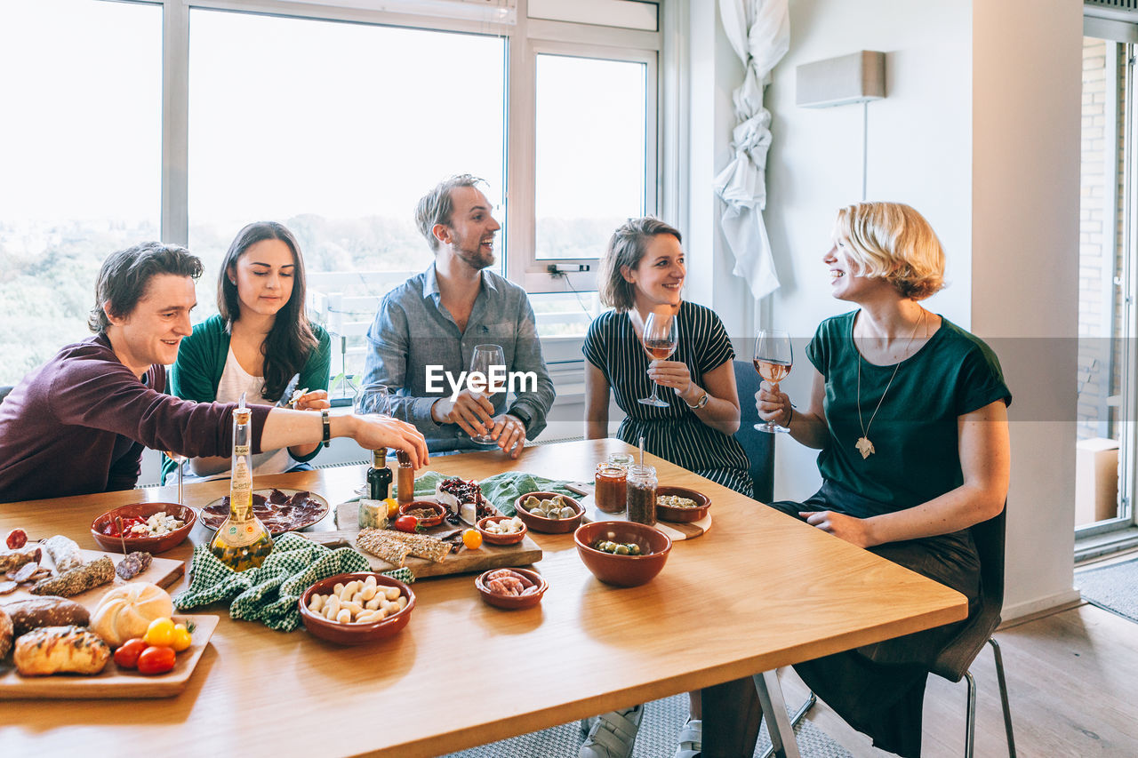 Friends Sitting On Table At Home