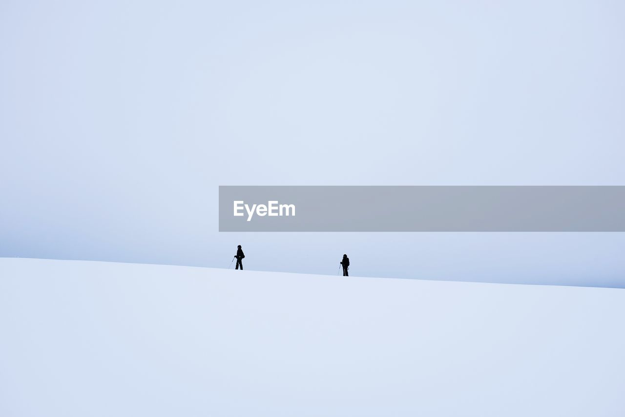 Low Angle View Of People Walking On Snow Covered Landscape Against Clear Sky