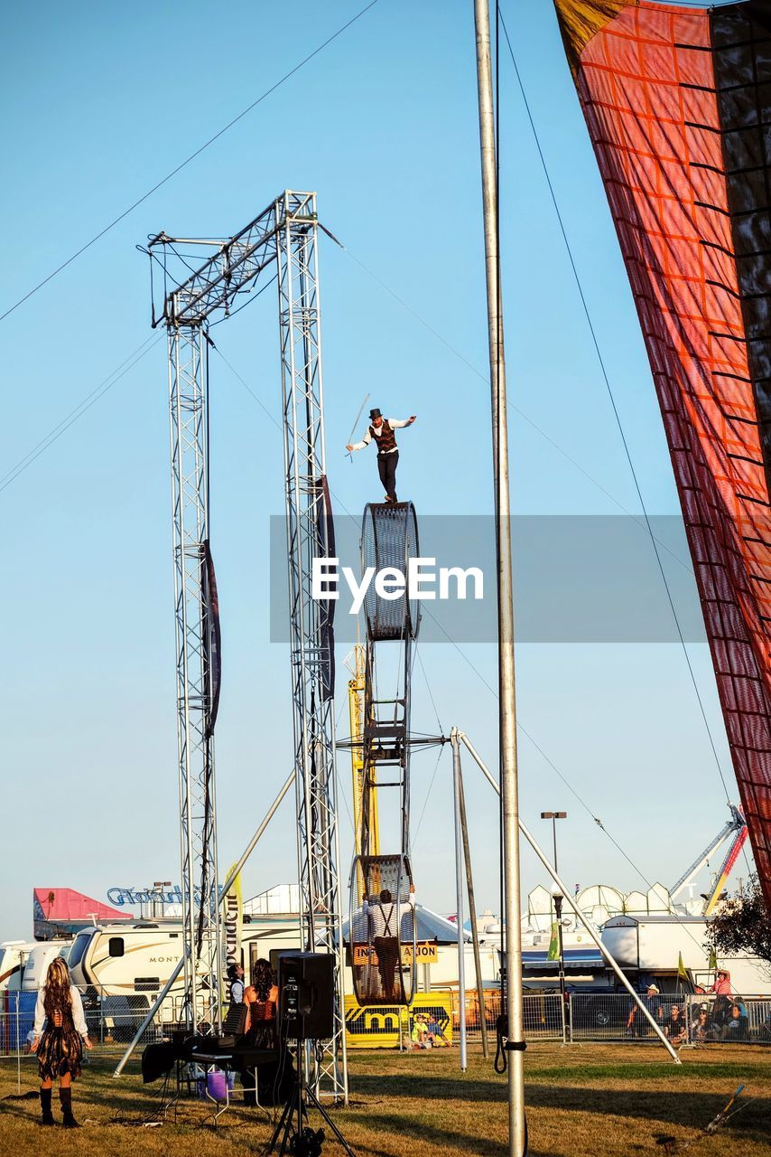 real people, construction site, architecture, built structure, day, low angle view, outdoors, occupation, building - activity, men, working, one person, clear sky, sky, building exterior