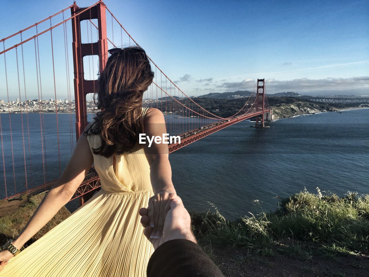 Rear View Of Woman Holding Man Hand In Front Of Golden Gate Bridge