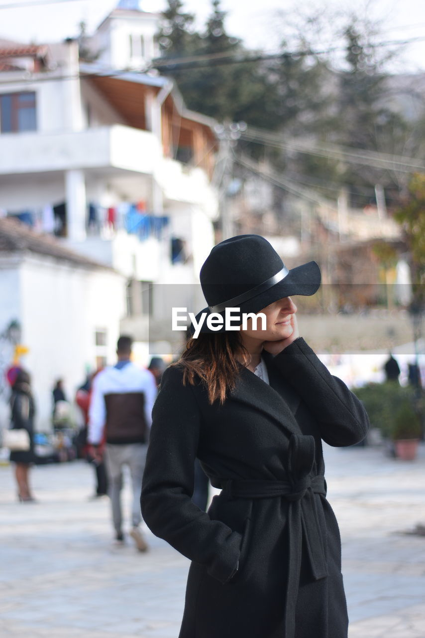 YOUNG WOMAN WEARING HAT STANDING AGAINST CITY