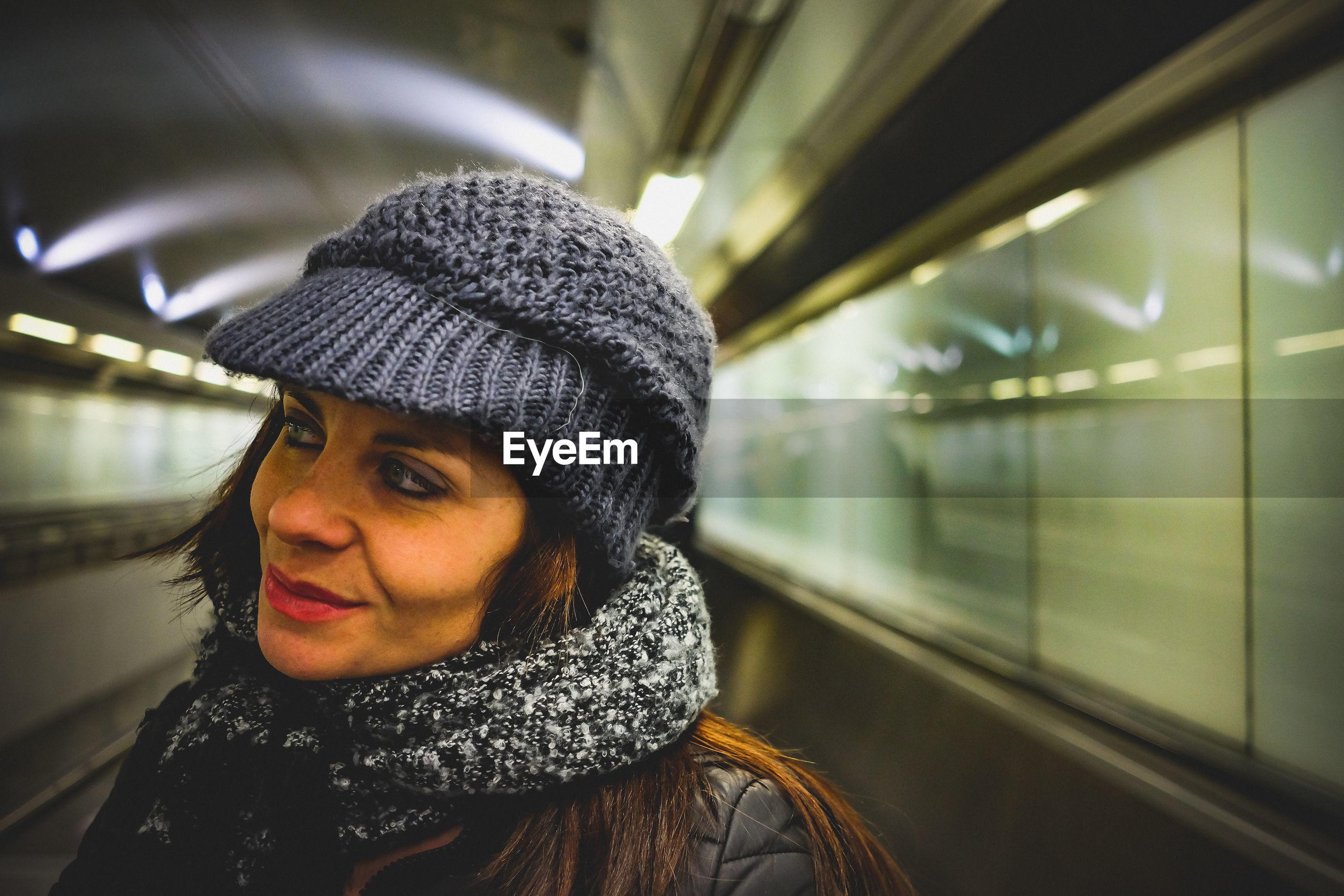 Thoughtful woman looking away at subway station
