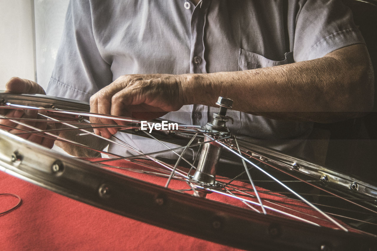 Midsection Of Mechanic Repairing Bicycle Wheel At Workshop