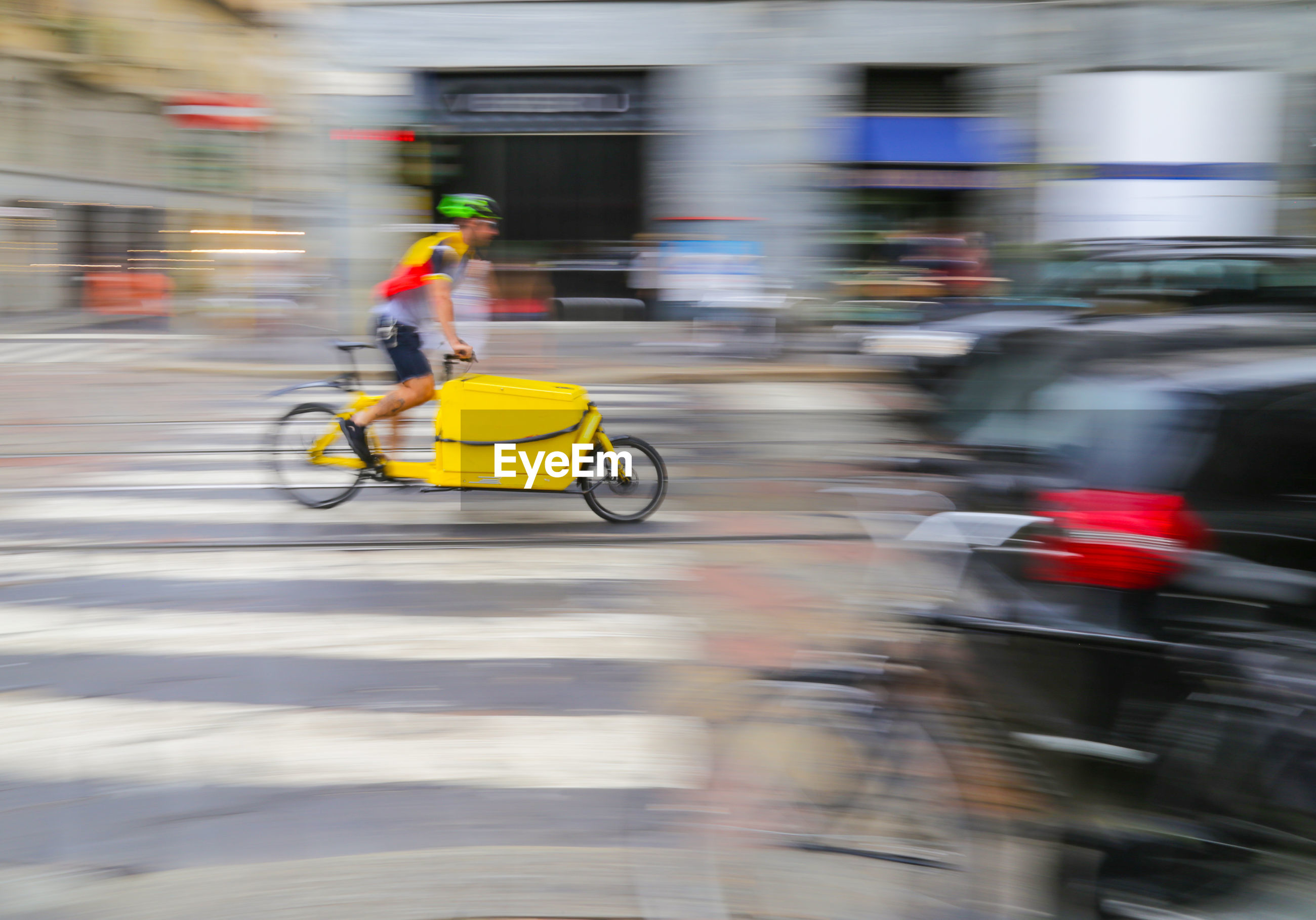 Blurred motion background with man riding a delivery bicycle on road