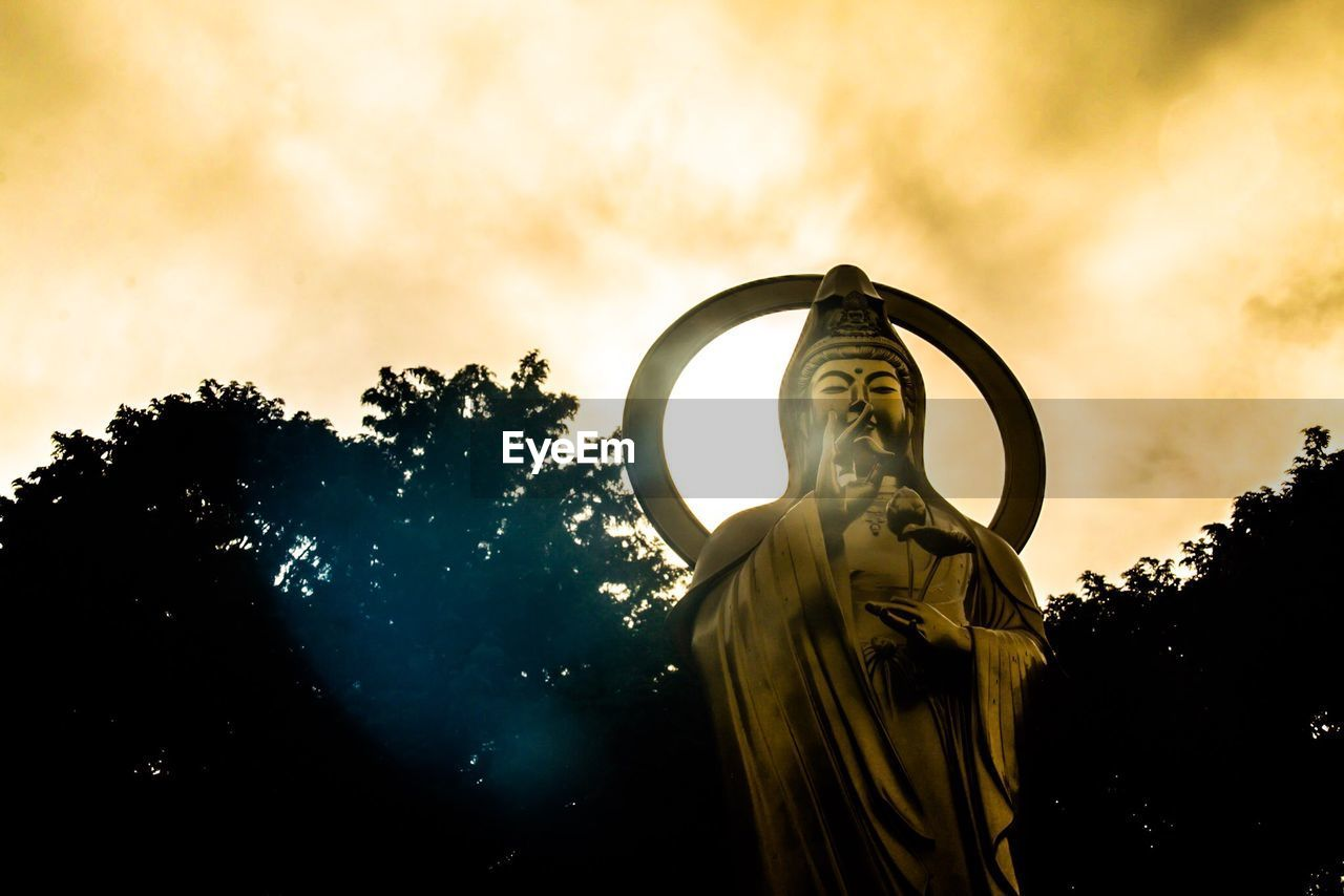 Low Angle View Of Gold Color Religious Statue And Trees Against Cloudy Sky During Sunset