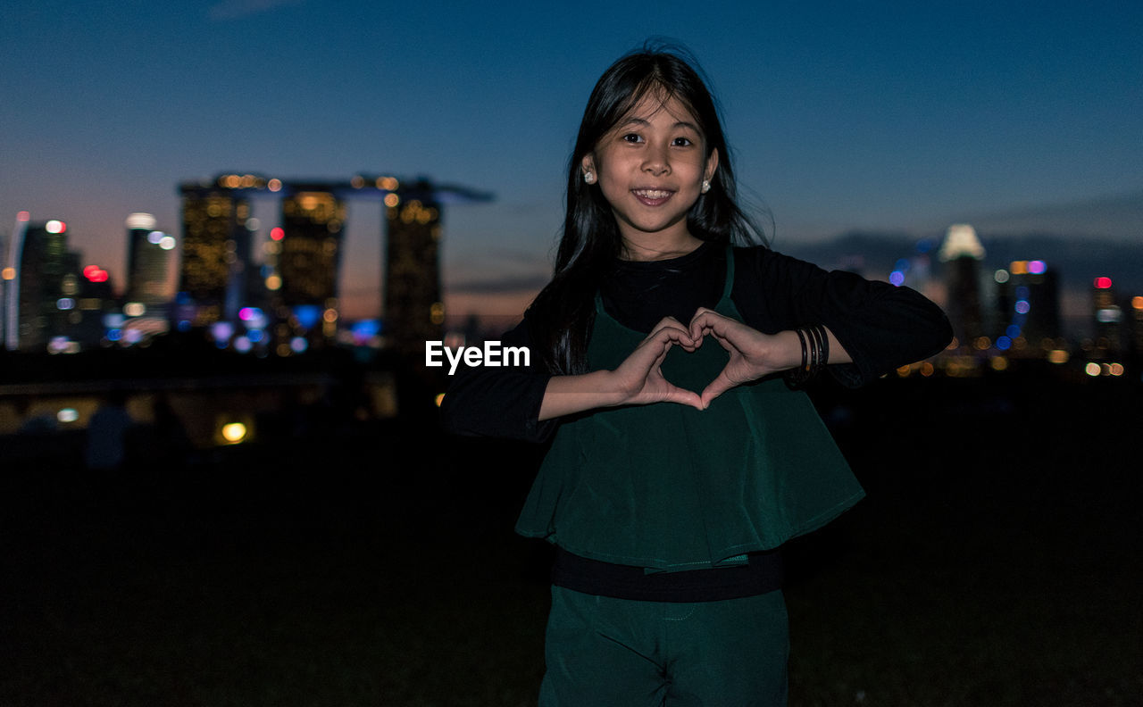 Portrait Of Girl Making Heart Shape While Standing In City At Night