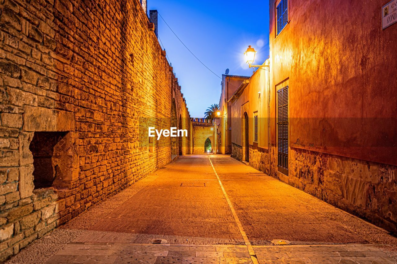 architecture, built structure, building exterior, direction, the way forward, building, street, city, residential district, wall - building feature, sky, illuminated, alley, road, diminishing perspective, wall, nature, footpath, narrow, transportation, no people, outdoors, long, stone wall