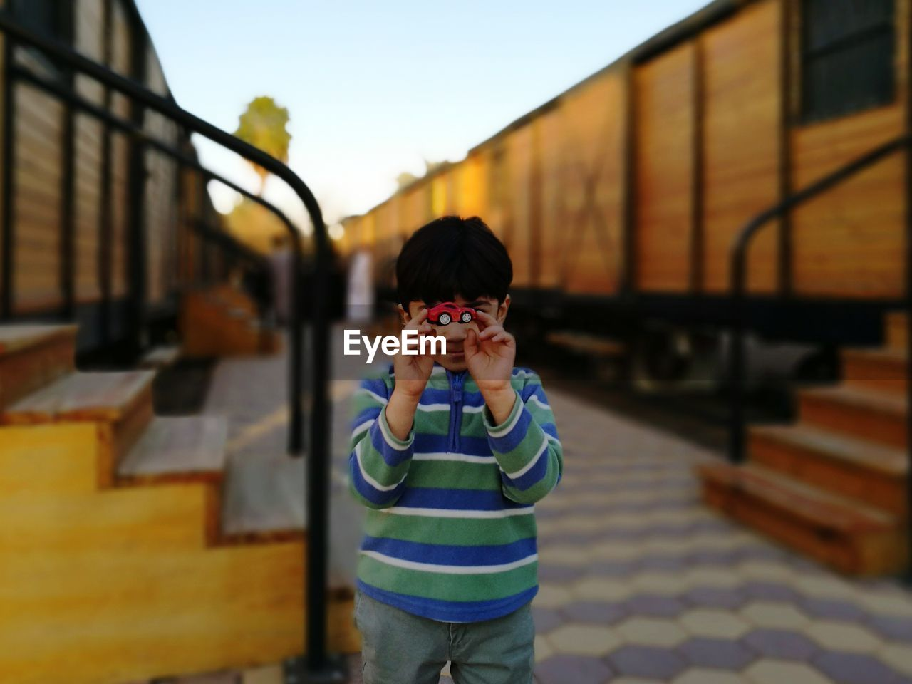Boy Holding Toy Car Amidst Freight Trains