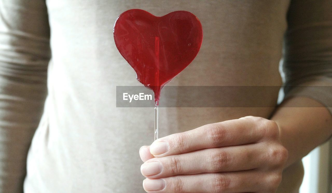 Mid section view of woman holding heart shape lollipop