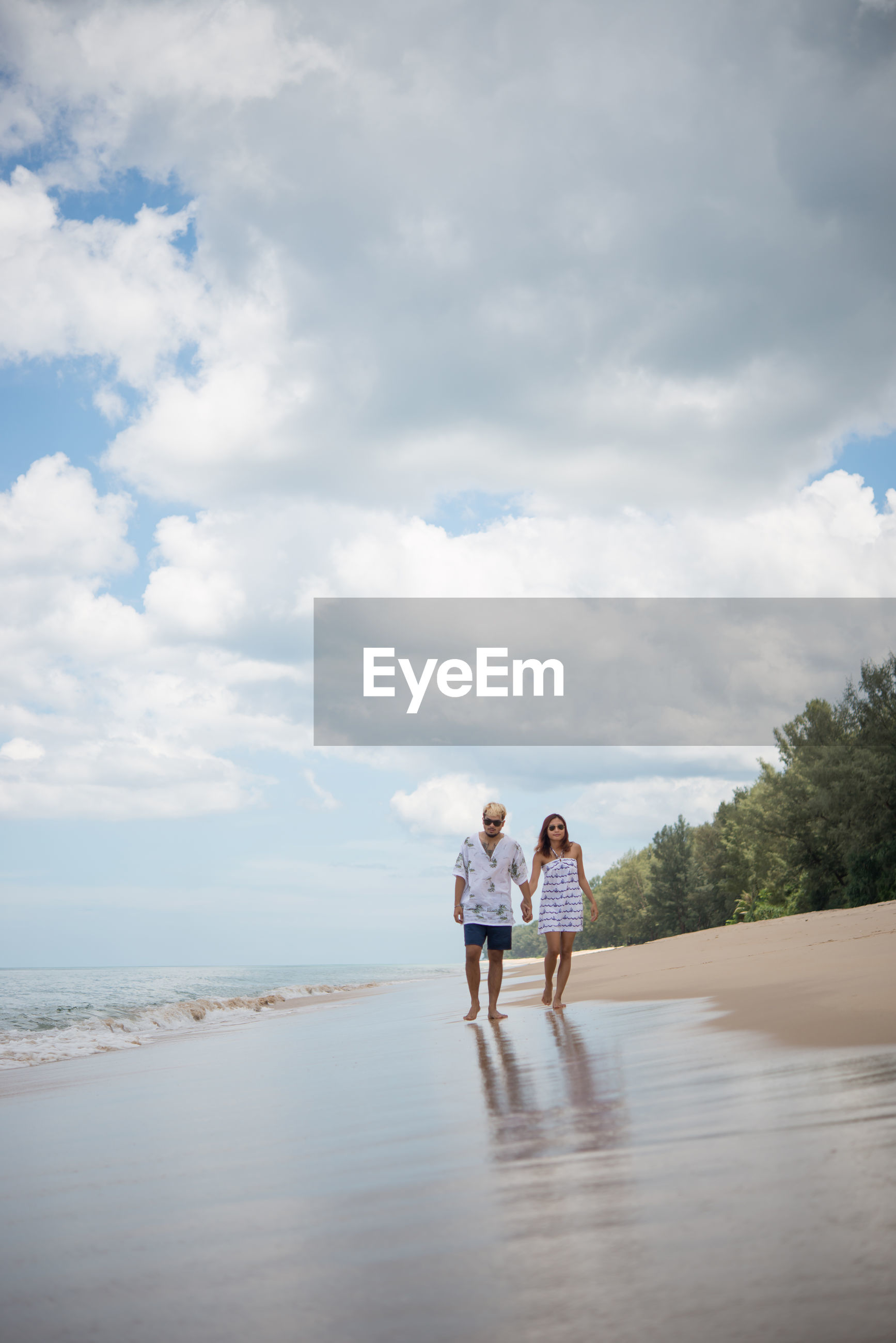 Man and woman walking at beach against sky