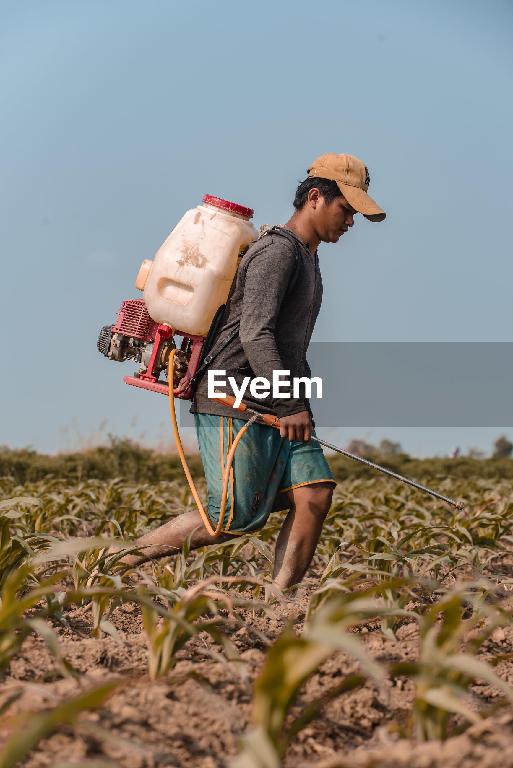 Farmer spraying pesticide on agricultural field against clear sky