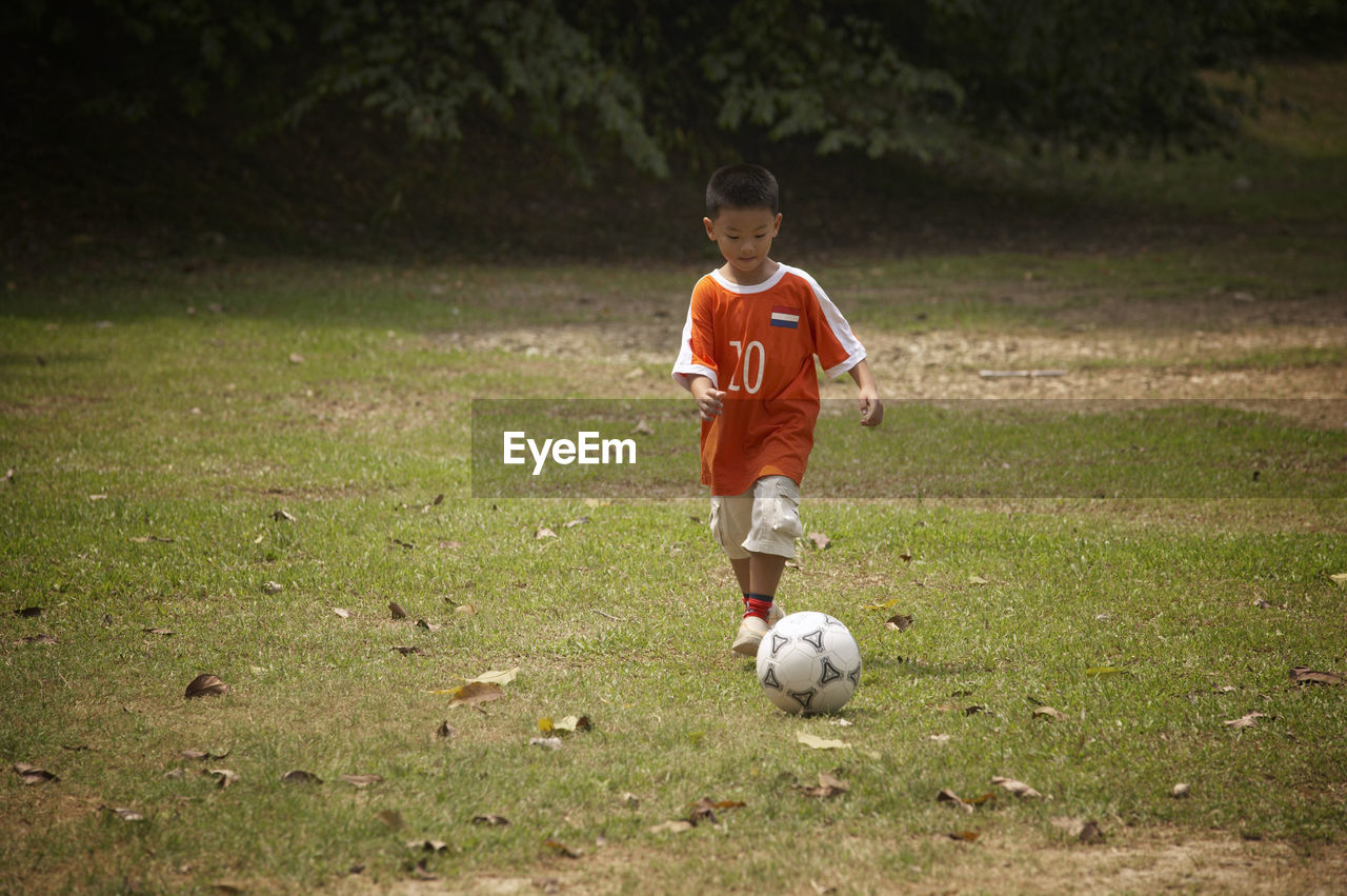 Full Length Of Boy Playing Soccer On Field At Park