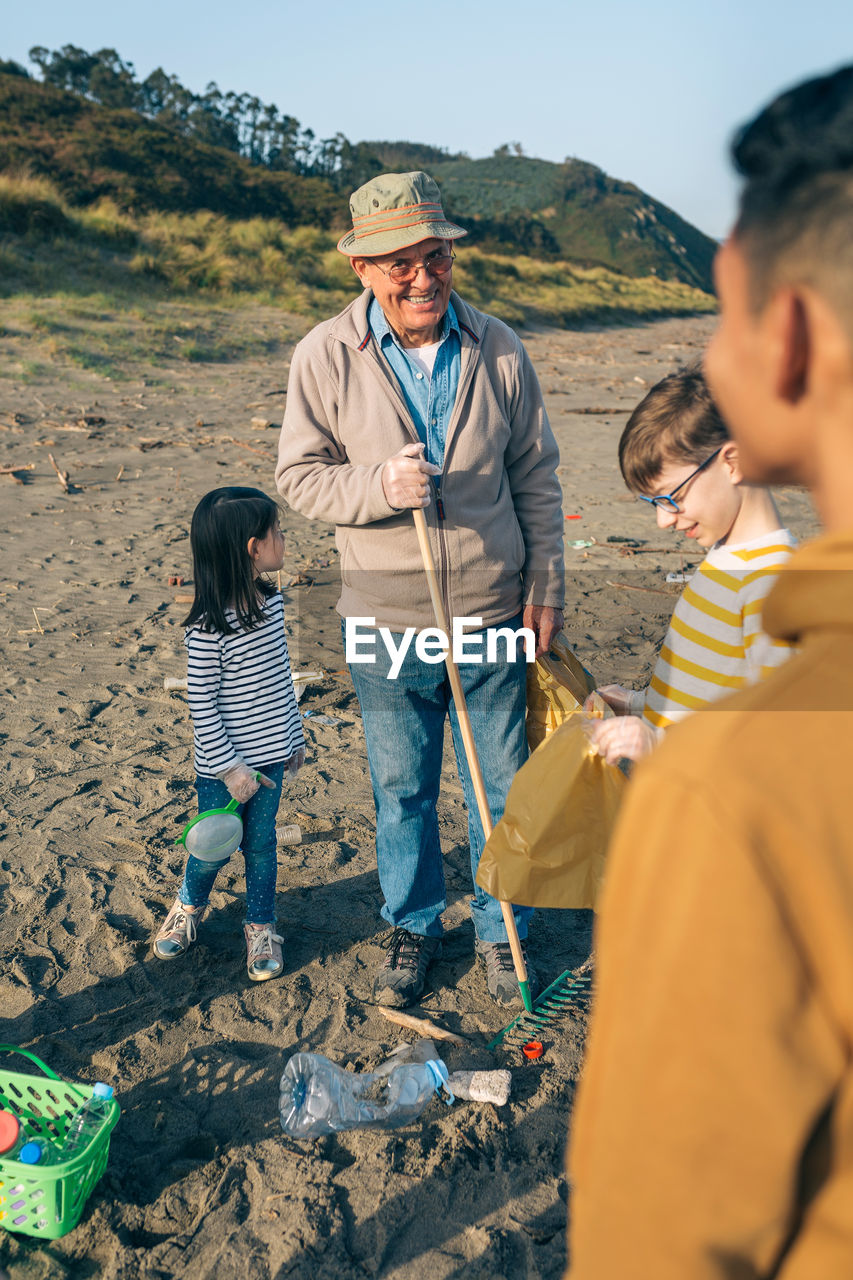 Grandfather smiling while standing with grandchildren at beach