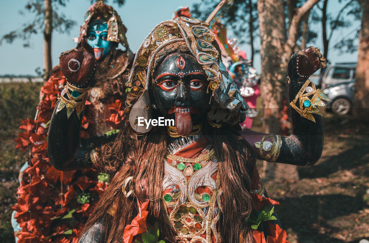 mask, mask - disguise, day, disguise, focus on foreground, creativity, art and craft, real people, costume, celebration, representation, nature, outdoors, people, front view, arts culture and entertainment, leisure activity, portrait, festival, obscured face