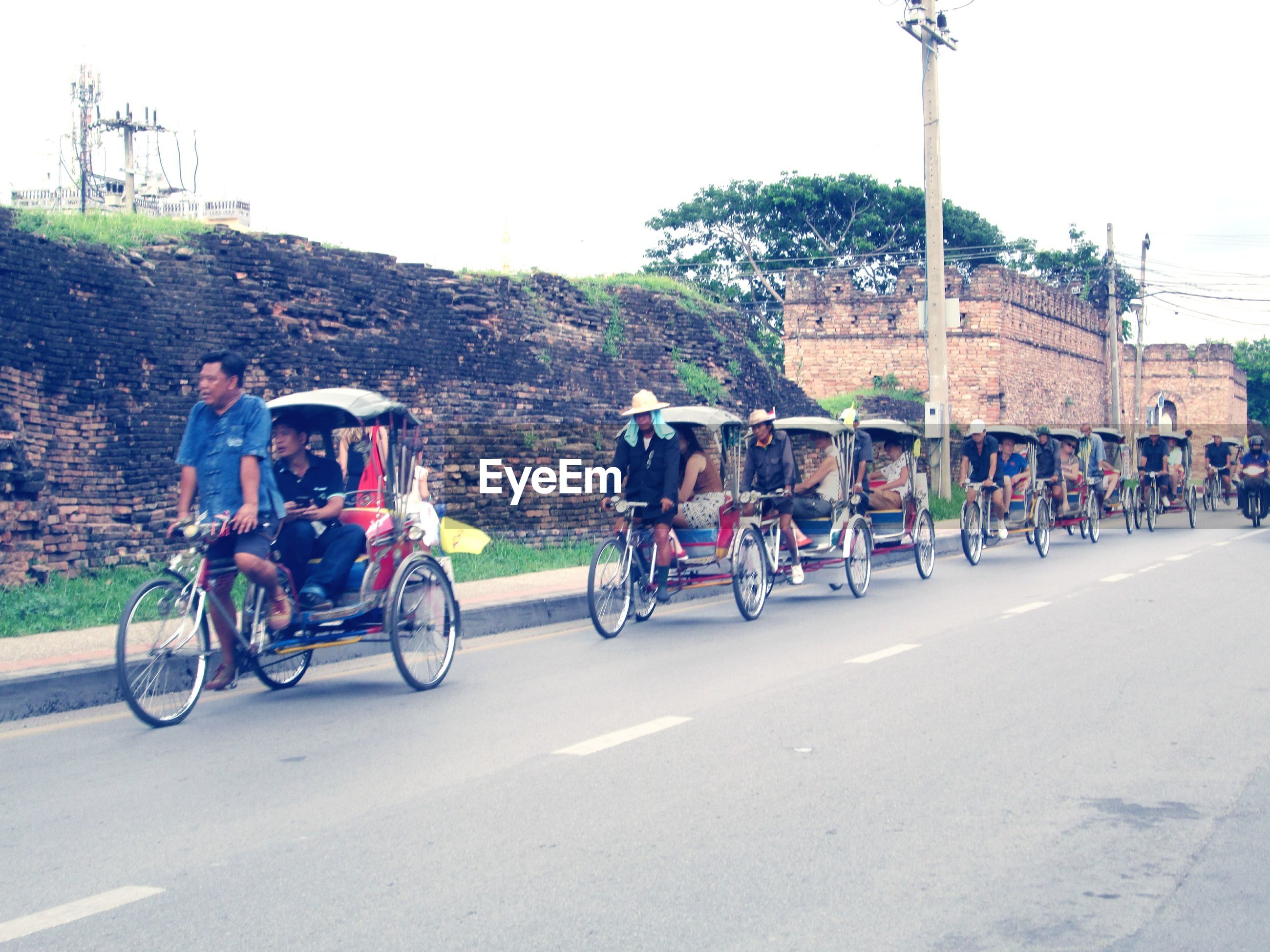 transportation, road, group of people, street, city, men, land vehicle, real people, mode of transportation, nature, people, day, lifestyles, sky, adult, women, ride, riding, bicycle