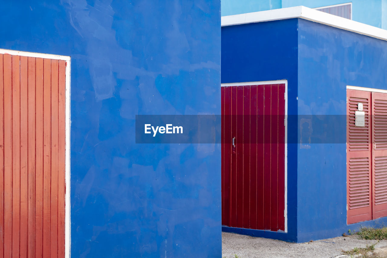 CLOSED DOOR OF BUILDING WITH BLUE WALL