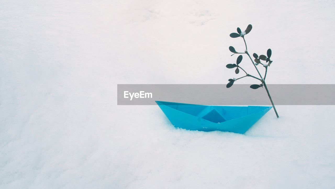 High Angle View Of Blue Paper Boat On Snow
