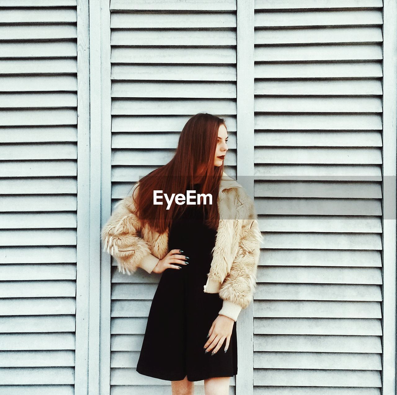 Fashionable Young Woman Standing Against Shutter