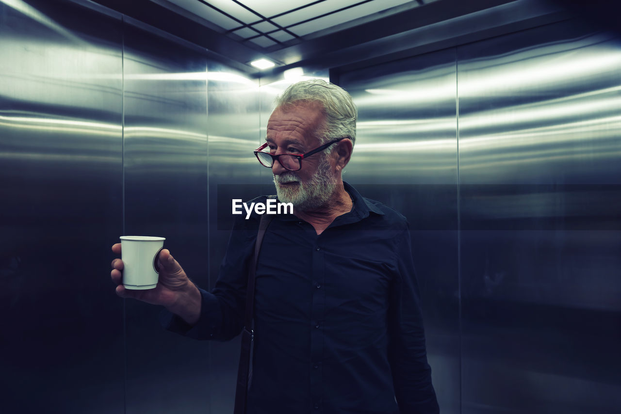Man holding coffee cup while standing in elevator