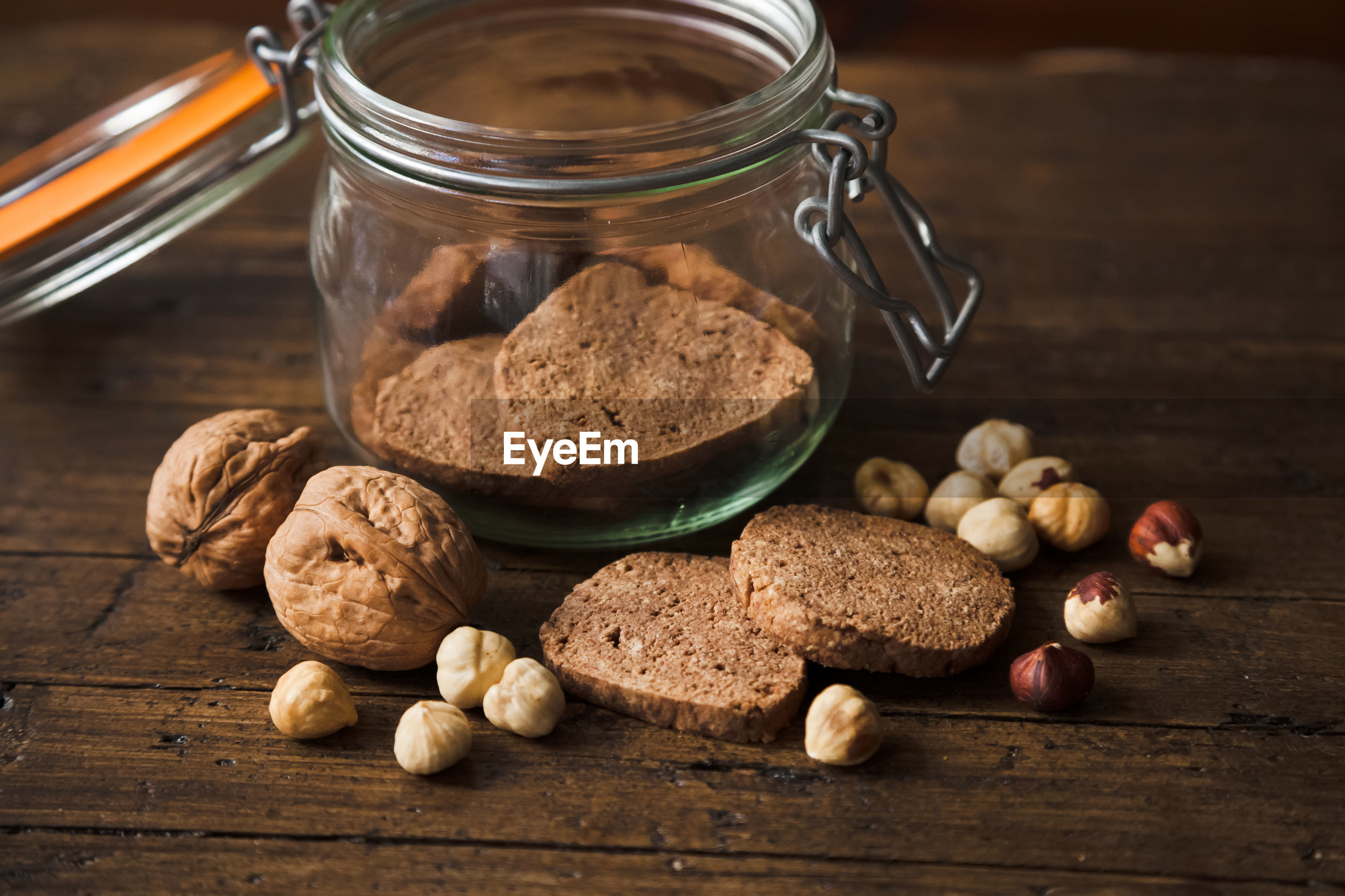 Close-up of cookies in jar by nuts on table