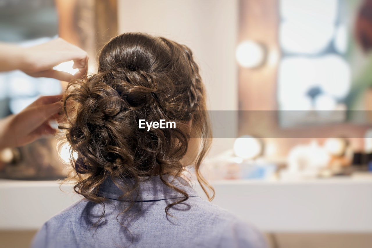 Hairdresser adjusting woman hair at home