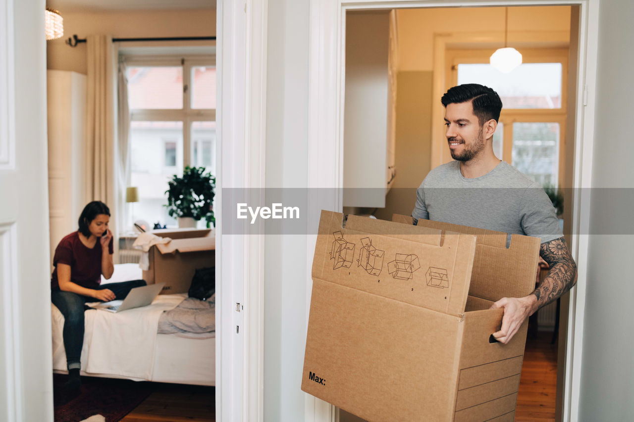 Smiling man carrying box from doorway towards woman using laptop in bedroom