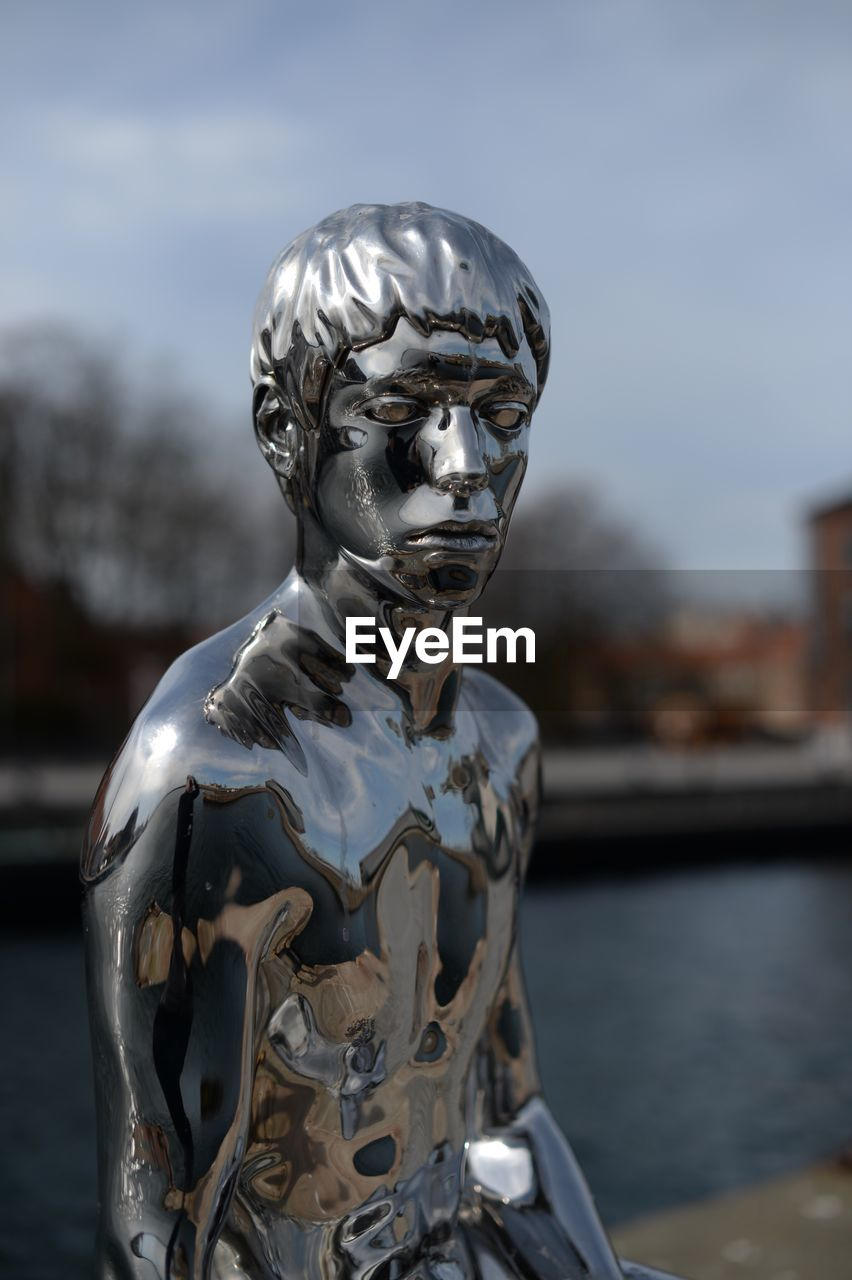 CLOSE-UP OF STATUE IN RIVER AGAINST SKY