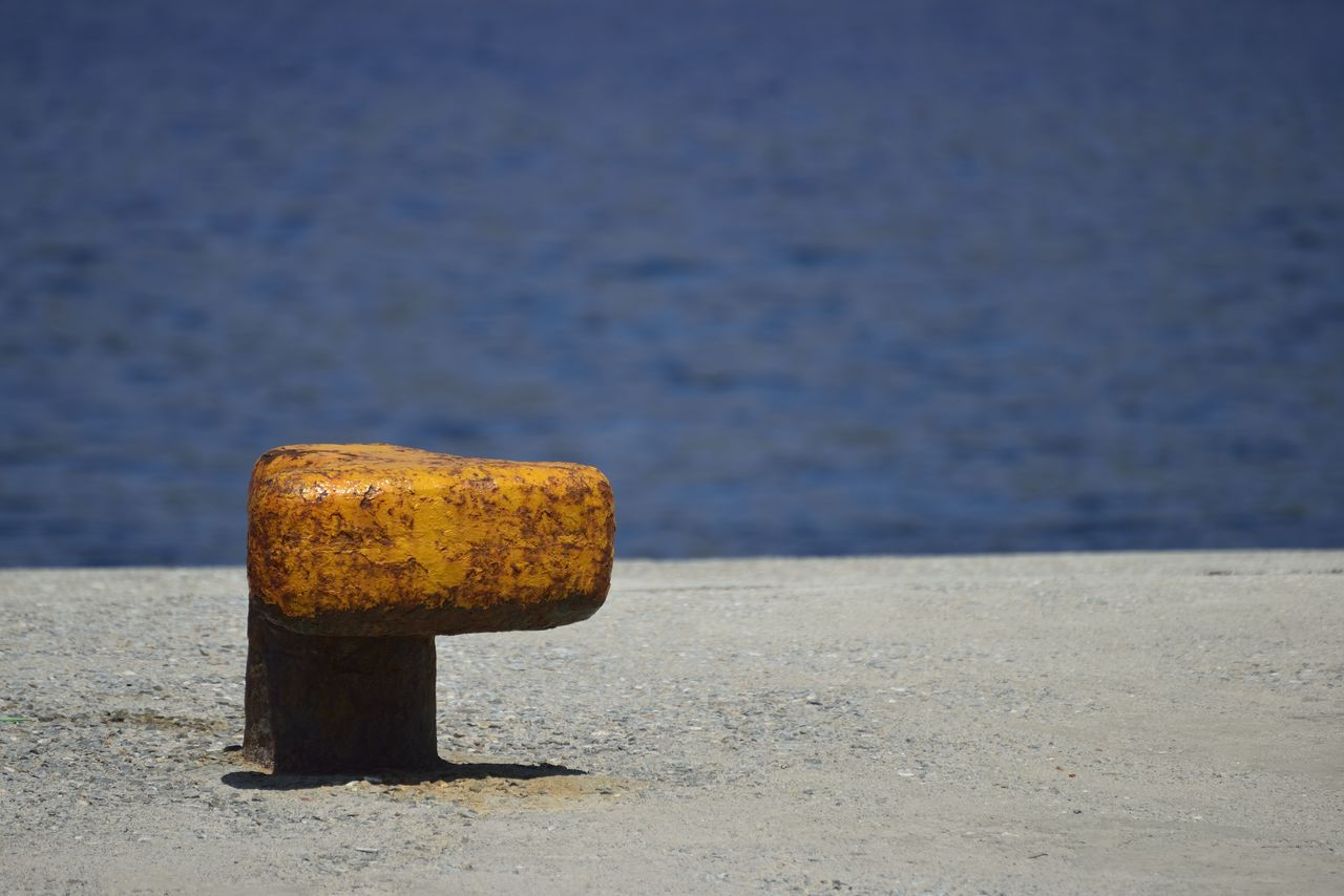 metal, no people, close-up, rusty, day, focus on foreground, post, water, outdoors, bollard, yellow, sunlight, nature, still life, wood - material, selective focus, land, weathered, beach, concrete
