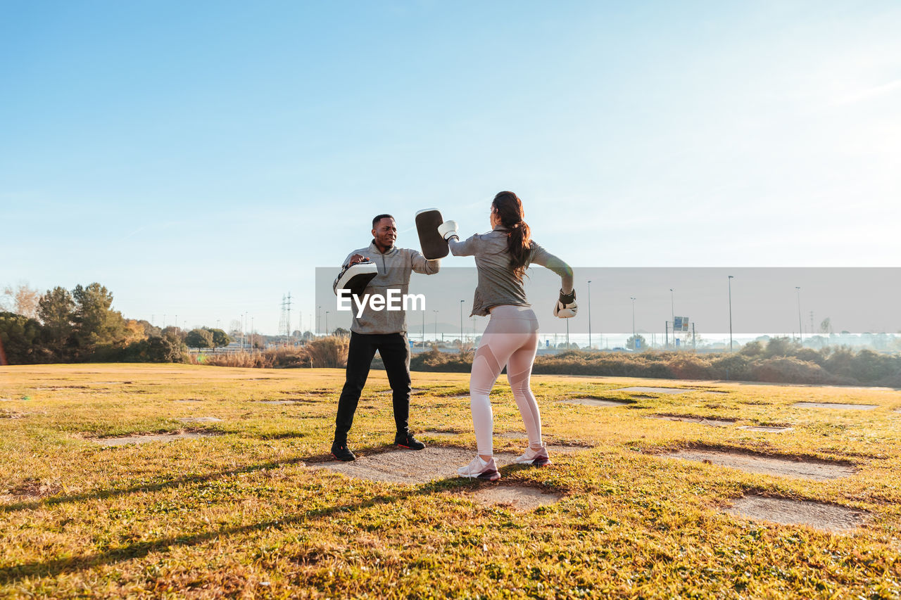 Full length of woman and man exercising on field against sky
