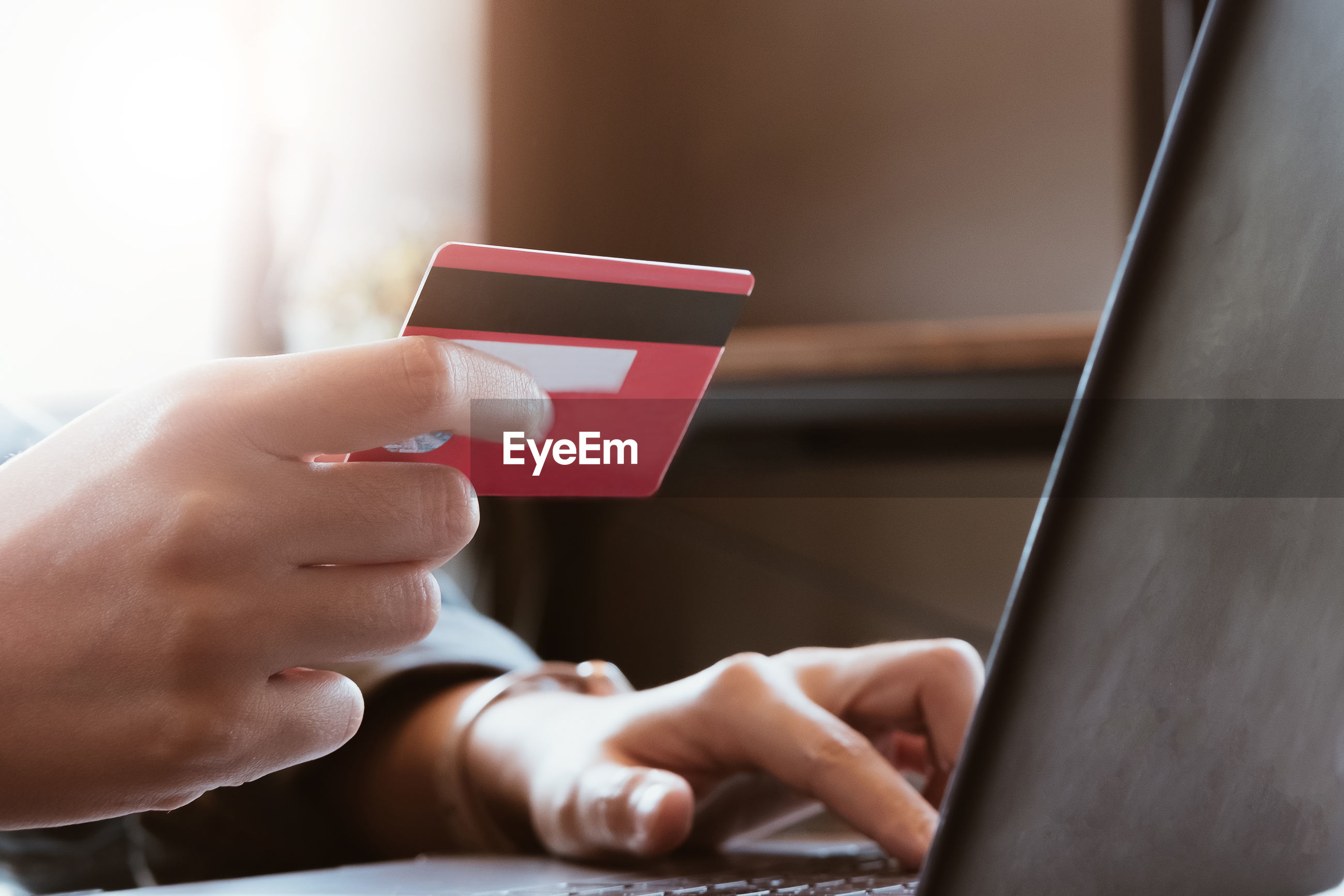 Cropped hands of person holding credit card while using laptop on table for online shopping