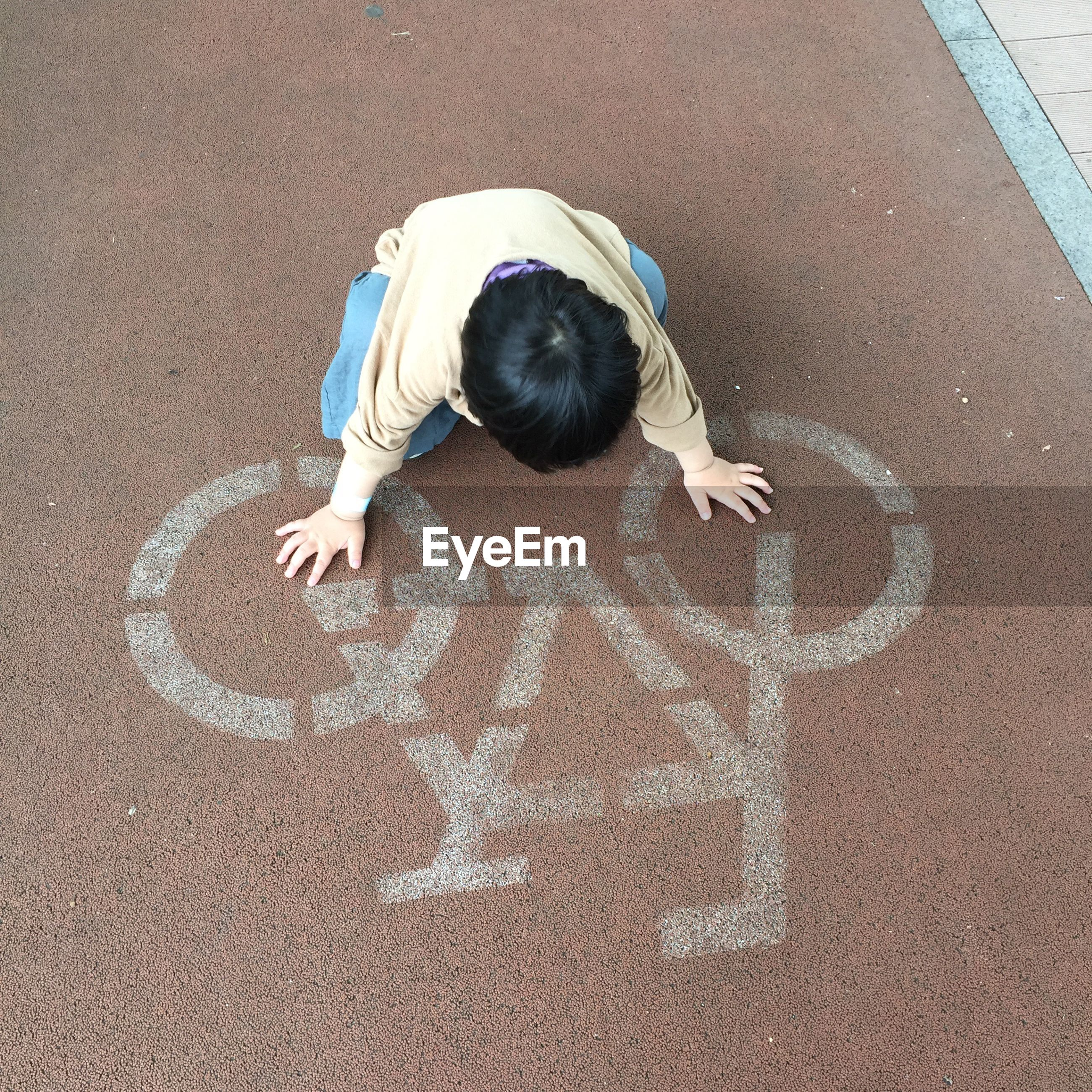 High angle view of boy kneeling on road marking