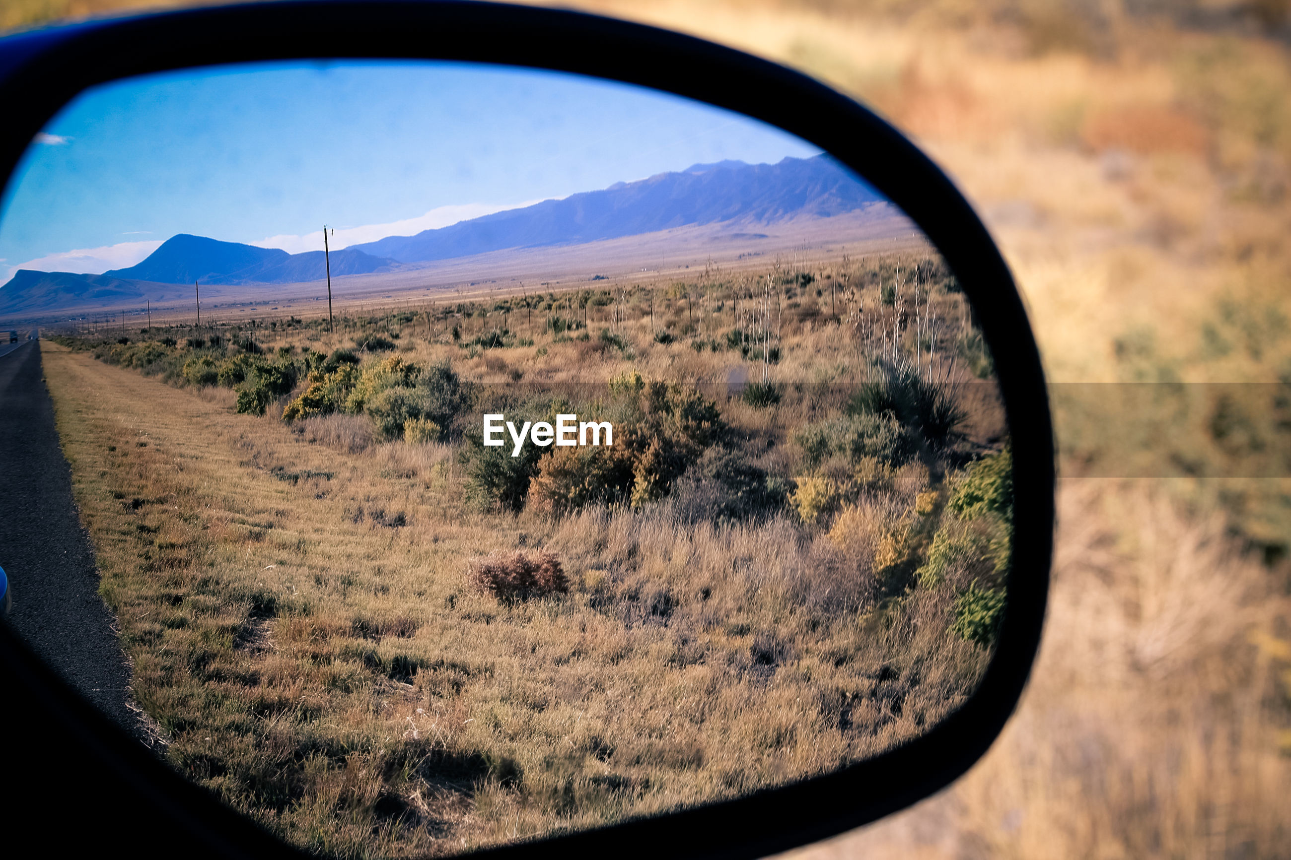 Reflection of landscape in side-view mirror