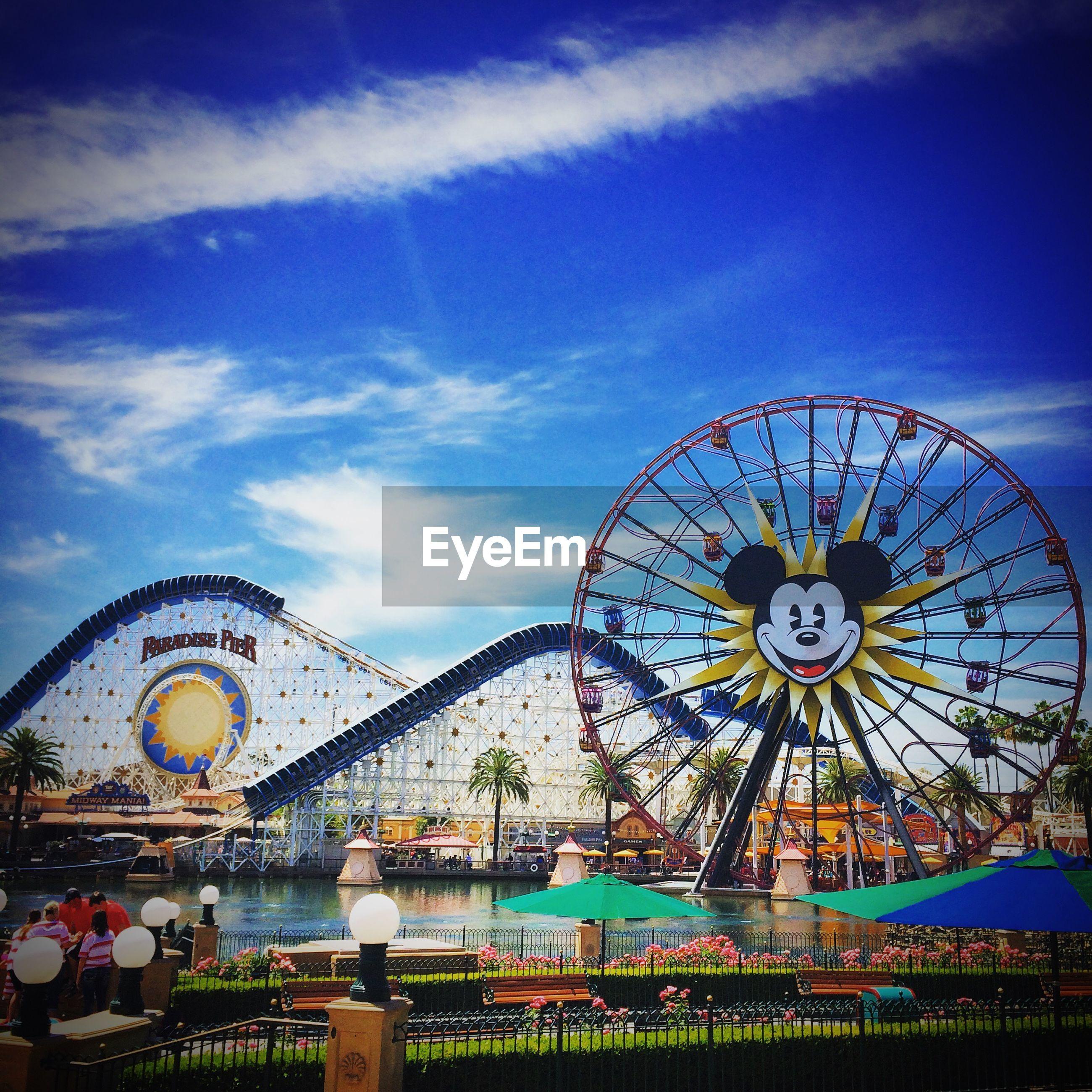amusement park, ferris wheel, amusement park ride, sky, arts culture and entertainment, cloud - sky, architecture, circle, built structure, time, low angle view, blue, famous place, clock, cloud, tourism, travel, travel destinations, day, outdoors