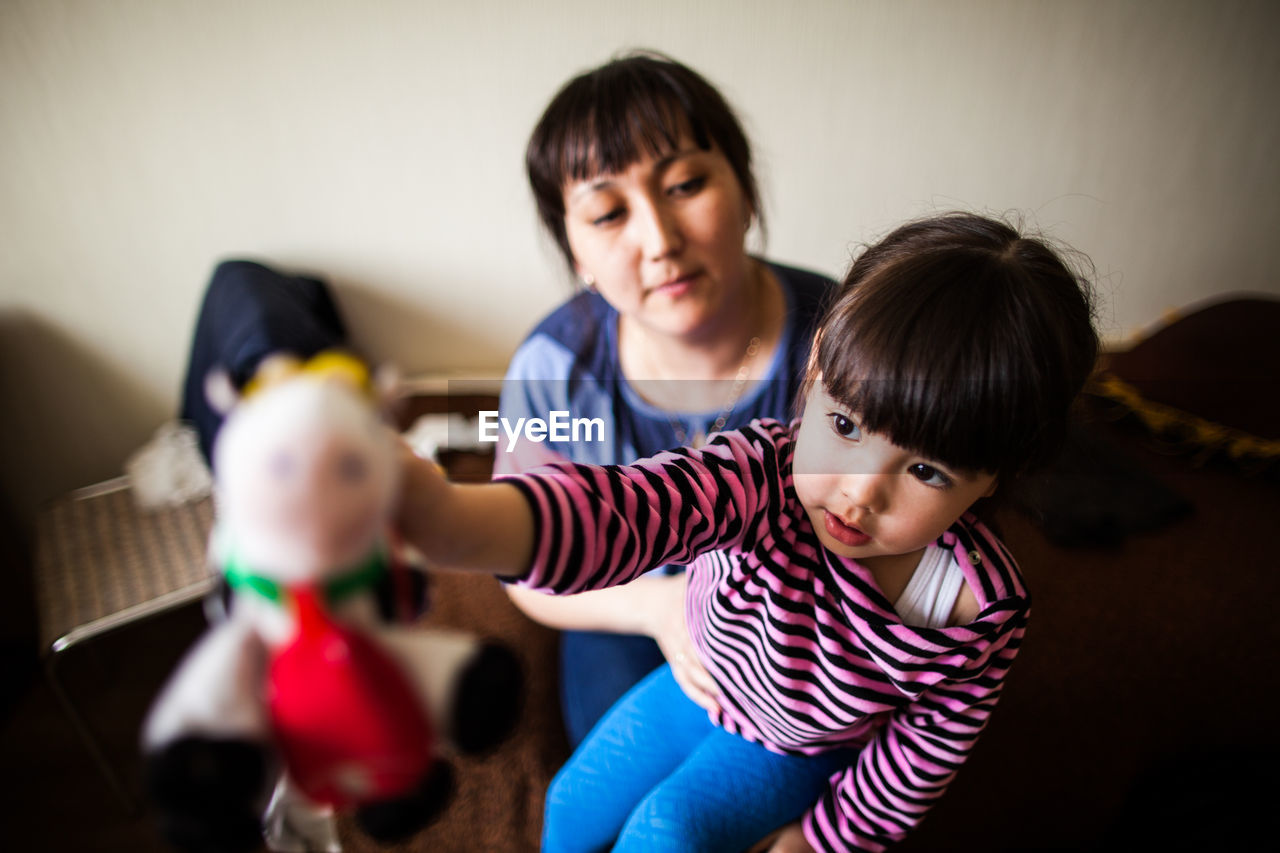 PORTRAIT OF HAPPY MOTHER WITH DAUGHTER AT HOME