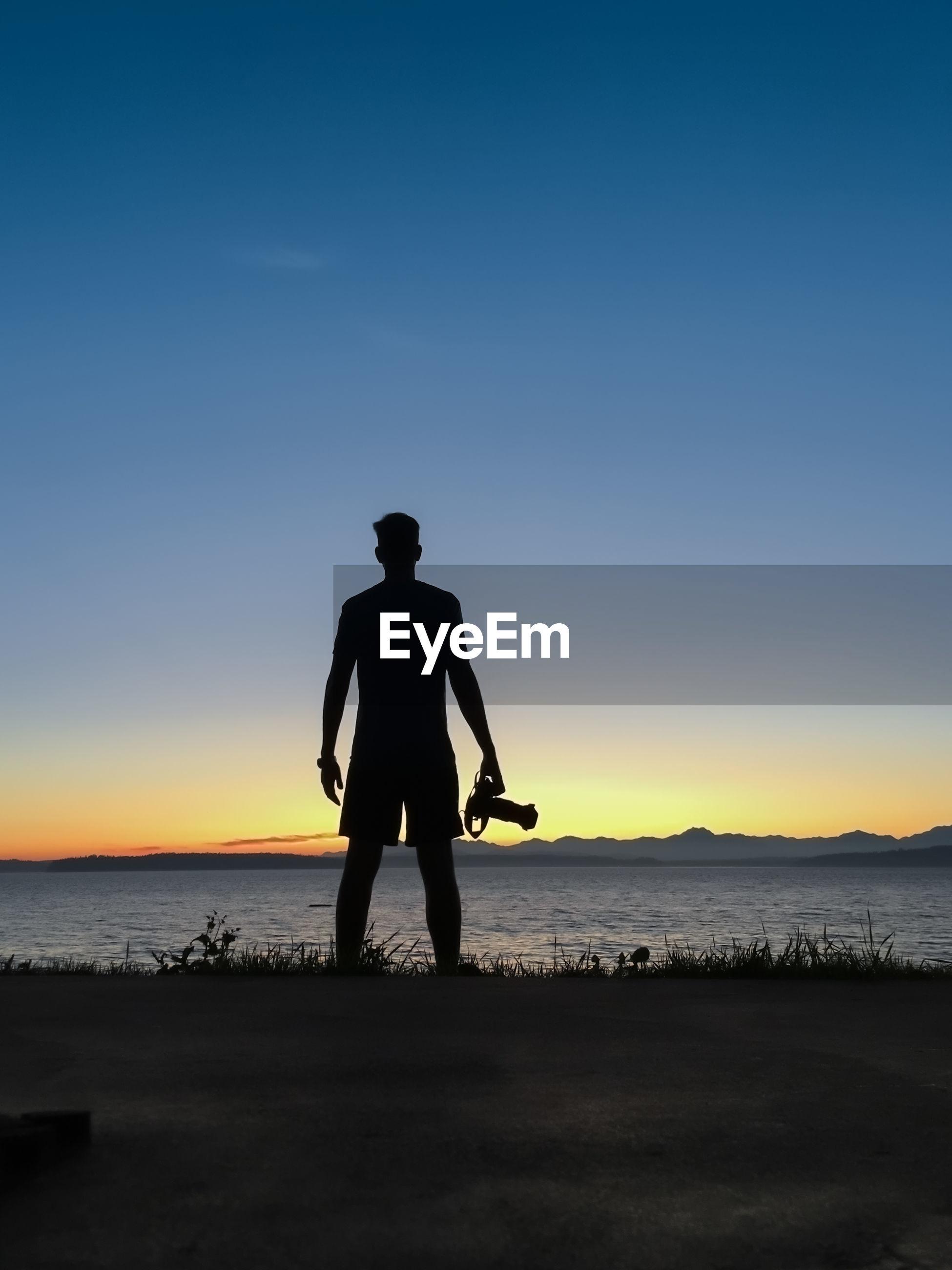 Silhouette man standing on shore against blue sky