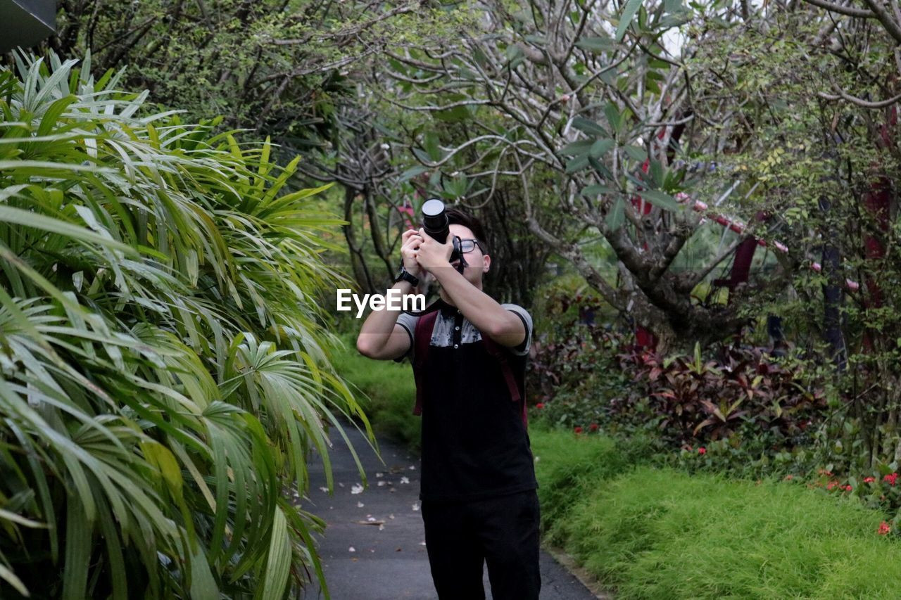 Man standing on footpath by plants photographing in gardens by the bay