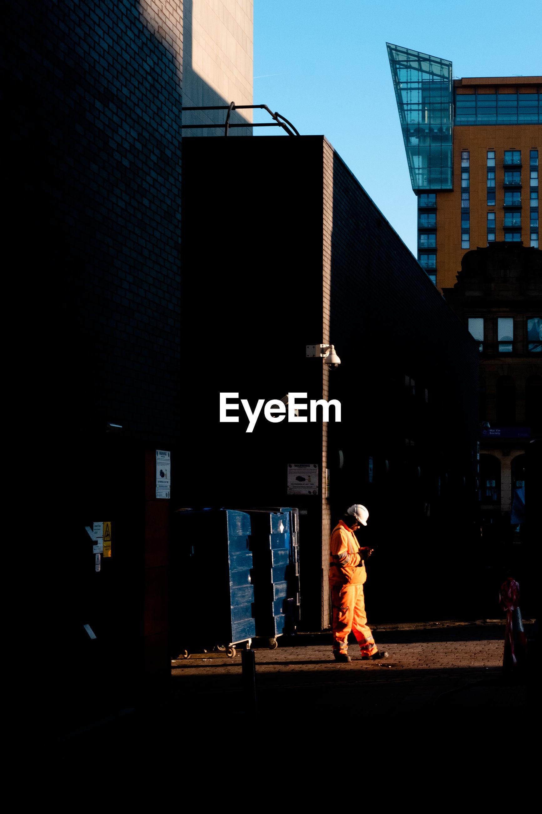 WOMAN WALKING ON STREET AGAINST BUILDINGS IN CITY