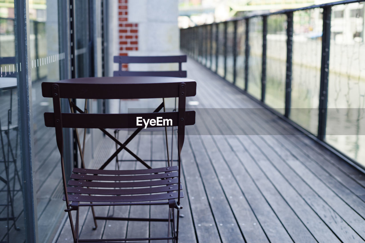empty, seat, no people, focus on foreground, day, architecture, absence, wood - material, built structure, chair, metal, outdoors, railing, footpath, the way forward, nature, bench, building exterior, wood
