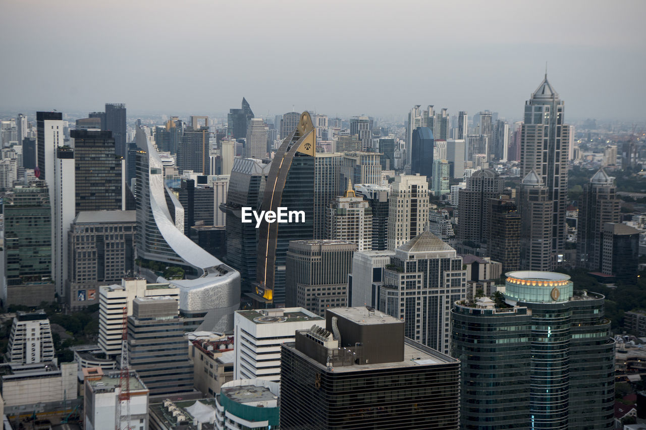 building exterior, built structure, city, architecture, building, cityscape, office building exterior, sky, tall - high, skyscraper, crowd, tower, modern, urban skyline, crowded, residential district, office, high angle view, nature, financial district, outdoors, spire, settlement, high