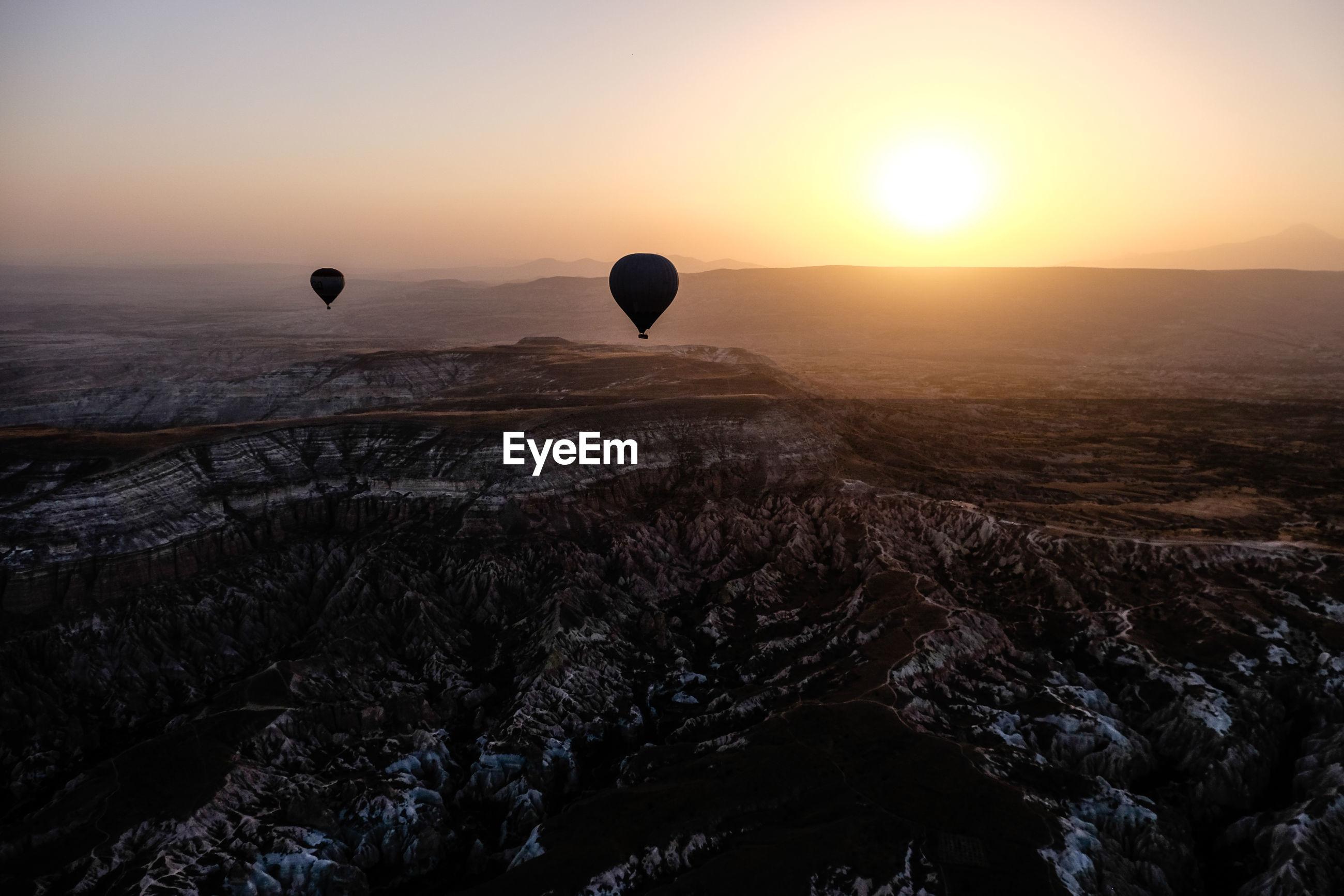 Hot air balloons flying over landscape against sky during sunrise