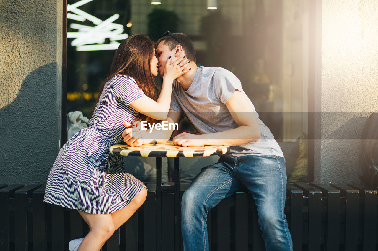 Young couple kissing at outdoor cafe in city