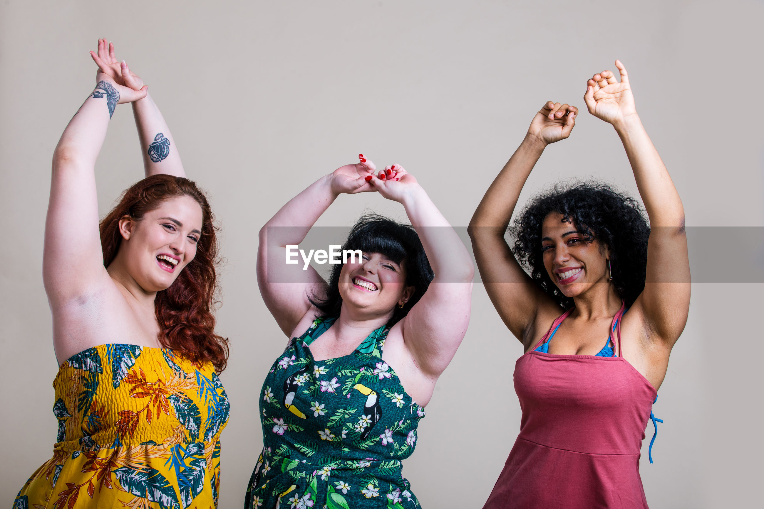 Portrait of smiling young women with arms raised against colored background