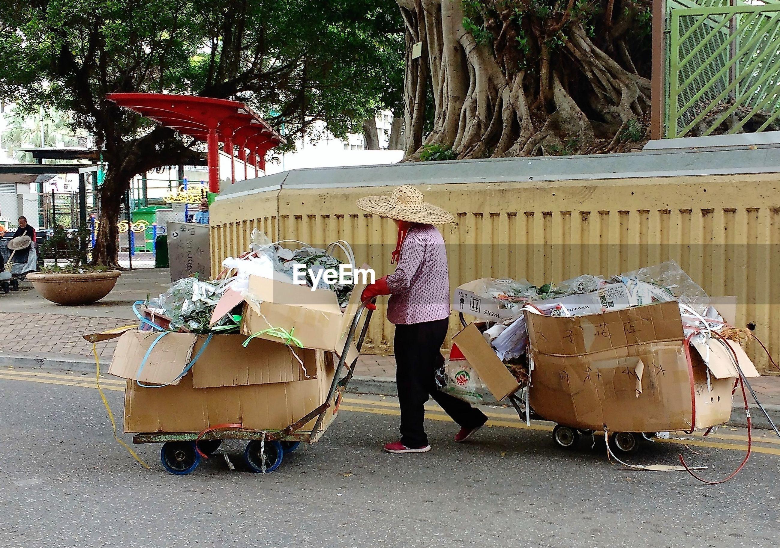 Woman pushing trash carts