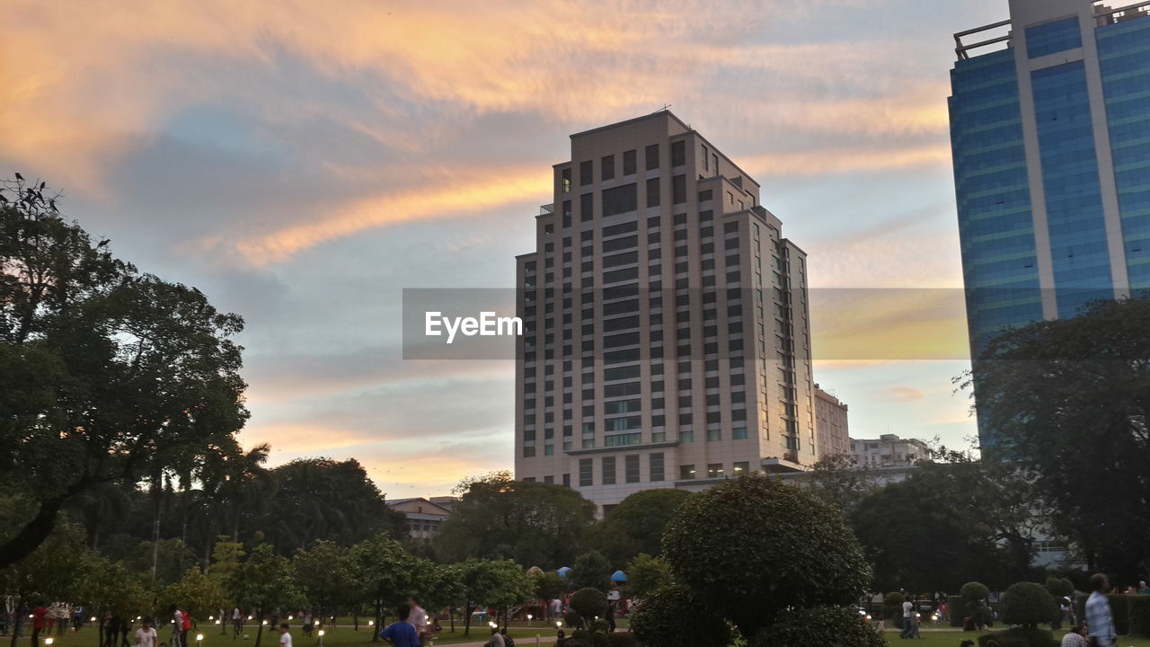 architecture, built structure, building exterior, sunset, sky, tree, cloud - sky, real people, skyscraper, outdoors, large group of people, city, day, people