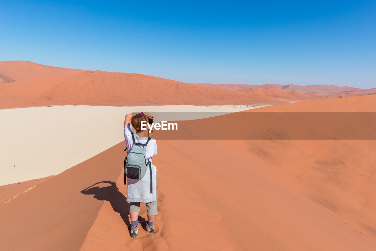 Rear view of woman photographing on desert against clear blue sky