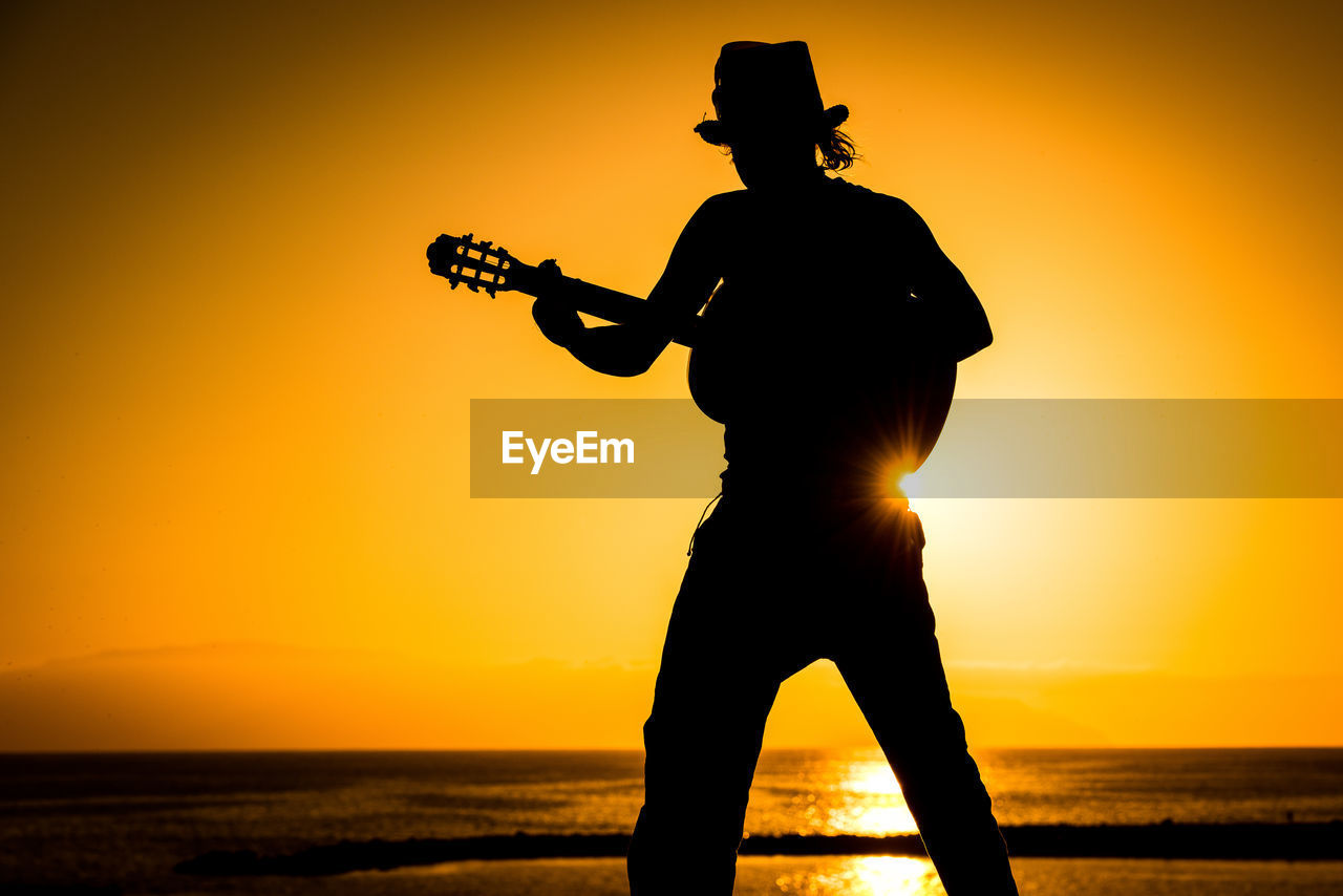 Silhouette man playing guitar at beach against orange sky