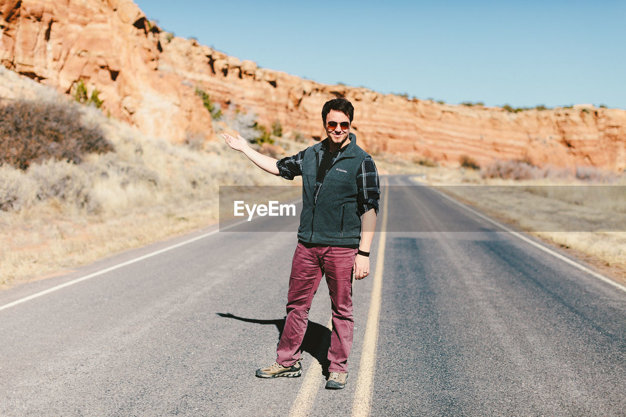 Full Length Of Smiling Man Gesturing While Standing On Road By Rock Formations
