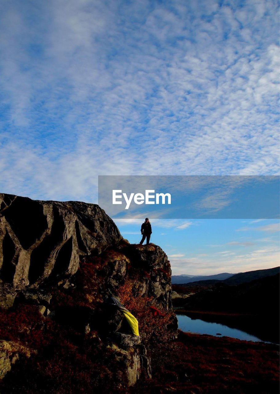 Woman standing on rock formation against sky