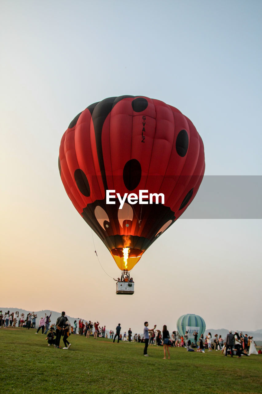 large group of people, real people, leisure activity, hot air balloon, sky, men, clear sky, women, lifestyles, outdoors, enjoyment, ballooning festival, sunset, fun, adventure, crowd, sport, standing, day, nature, people