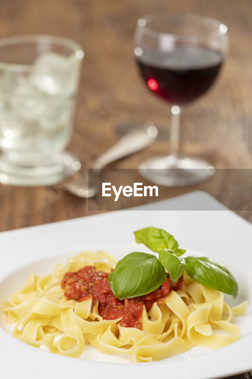 Close-up of pasta served in plate with wine on table